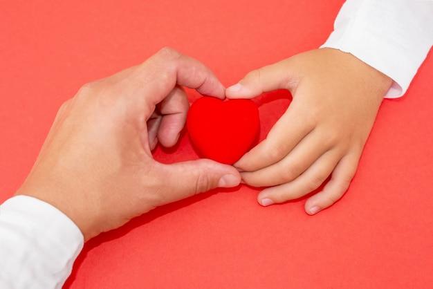 Corazón rojo en manos de un niño y una madre sobre un fondo rojo aislado. el concepto de amor, misericordia, simpatía.