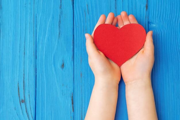 Corazón rojo en manos del niño
