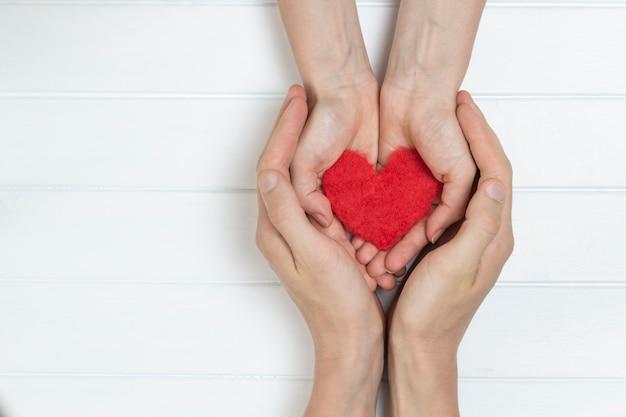 Corazón rojo en manos de una pareja amorosa de hombres y mujeres.