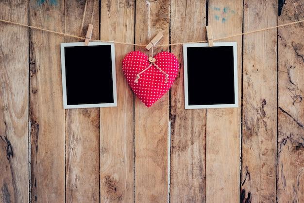 Corazón rojo y marco de dos fotos colgando de cuerda de cuerda con fondo de madera.