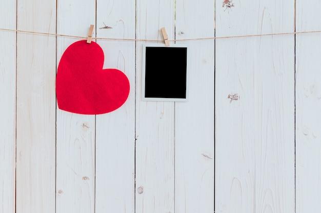 Corazón rojo y marco de foto en blanco colgando en cuerda para tender la ropa sobre fondo blanco de madera con espacio. día de san valentín.