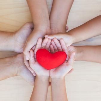 Corazón rojo en el padre y niños tomados de la mano juntos sobre fondo de madera.
