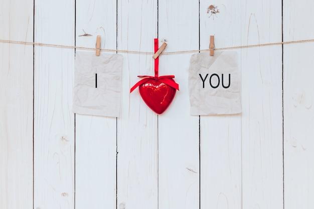 Corazón rojo y papel viejo con texto te amo colgando en cuerda para tender la ropa sobre fondo blanco de madera.