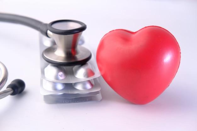 Corazón rojo. pastillas y estetoscopio en espacio en blanco