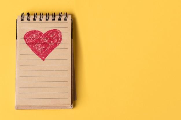 Un corazón rojo pintado en un cuaderno de papel reciclado sobre un fondo amarillo.