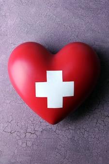 Corazón rojo con signo de cruz en la mesa de madera de color