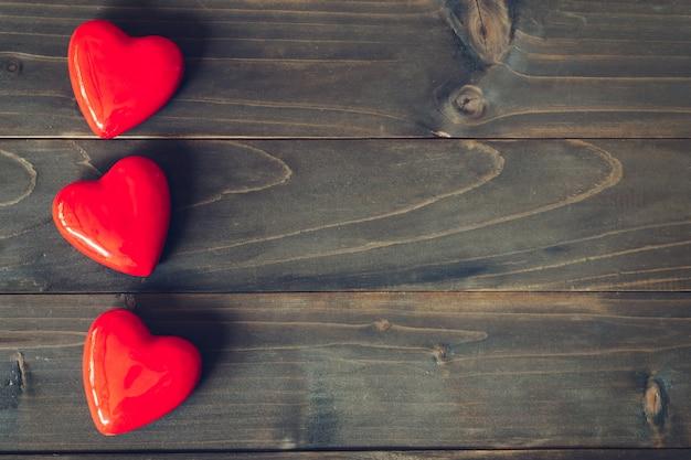 Corazón rojo sobre fondo de mesa de madera con espacio de copia