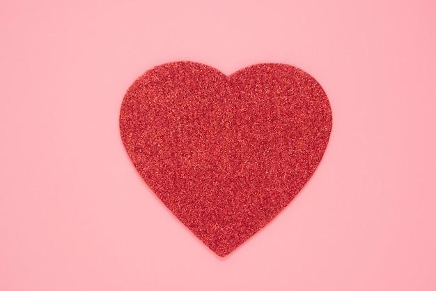 Corazón rojo sobre fondo rosa abstracto, amor, día de san valentín. endecha plana con copia espacio. corazón rojo brillante.