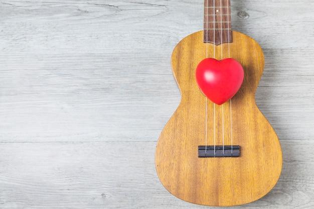 Corazón rojo sobre la guitarra de madera sobre el tablón de madera
