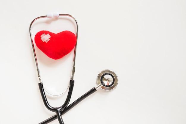 Corazón rojo suave con estetoscopio sobre fondo blanco
