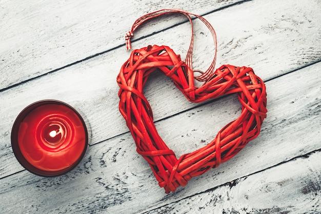 Corazón rojo y vela encendida sobre fondo blanco de madera. tarjeta de felicitación romántica en estilo vintage. fondo del día de san valentín