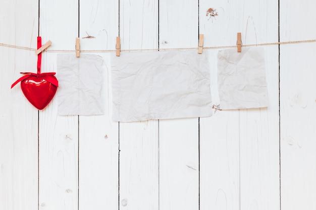 Corazón rojo y viejo papel en blanco colgando en cuerda para tender la ropa sobre fondo blanco de madera con espacio. día de san valentín.