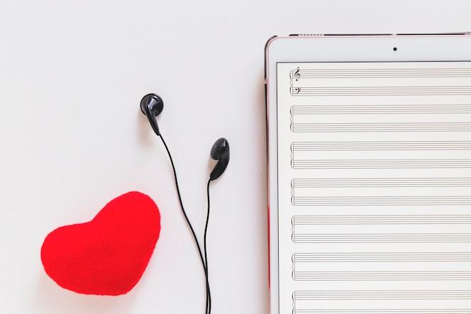 Corazón rojo y auricular con tableta digital sobre fondo blanco