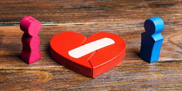 Un corazón rojo con un yeso y una pareja de amantes.