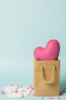 Corazón rosa en bolsa artesanal cerca de decoraciones