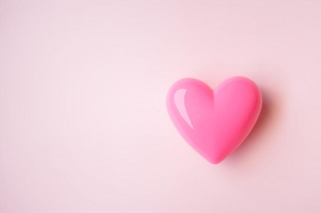 Corazón rosado en el fondo rosado para el día de tarjeta del día de san valentín