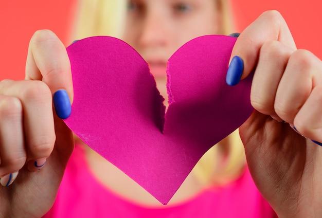 Corazón roto. mujer desgarrando el corazón por la mitad. divorcio, despedida, separación. problema de relación. ruptura de relaciones.