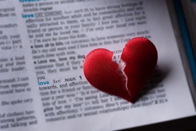 Corazón roto rojo en la definición de amor de diccionario. el concepto de corazón roto.