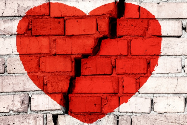 Corazón roto rojo en la pared de ladrillo con una gran grieta en el medio. concepto de amor roto