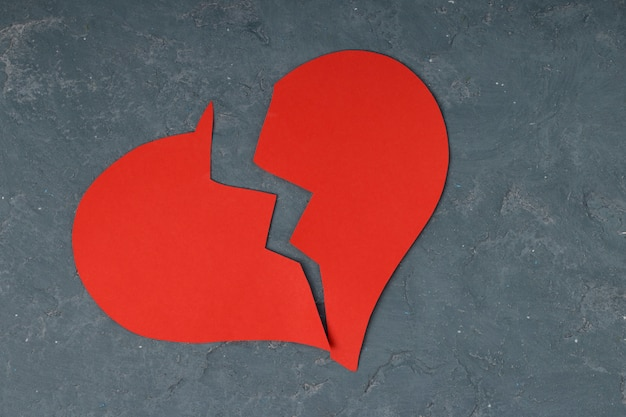 Corazón roto rojo sobre concreto
