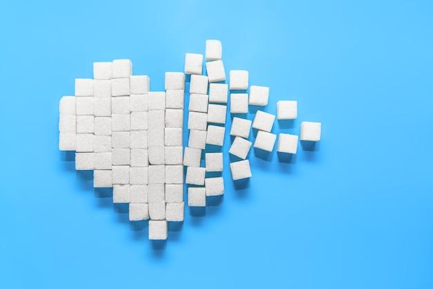Corazón roto de terrones de azúcar blanco puro en azul, el día mundial de la lucha contra la diabetes