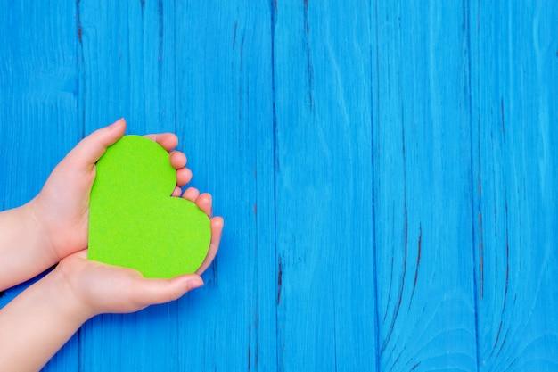 Corazón verde en manos del niño