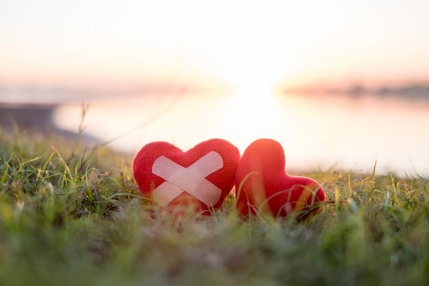 Corazón con yeso y corazón rojo en el fondo, cae el sol.
