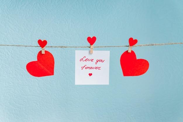 Corazones de amor de san valentín rojo alfileres colgando de cordón natural contra el fondo azul. te amo para siempre inscripción en trozos de papel.