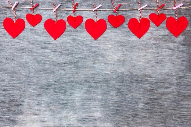 Corazones del amor de la tarjeta del día de san valentín roja en el fondo rústico de la textura de la madera de deriva, espacio de la copia