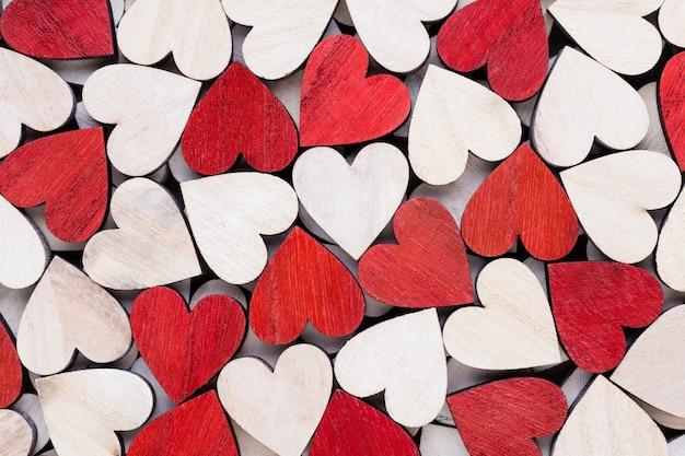 Corazones blancos y rojos, fondo con corazones de madera.
