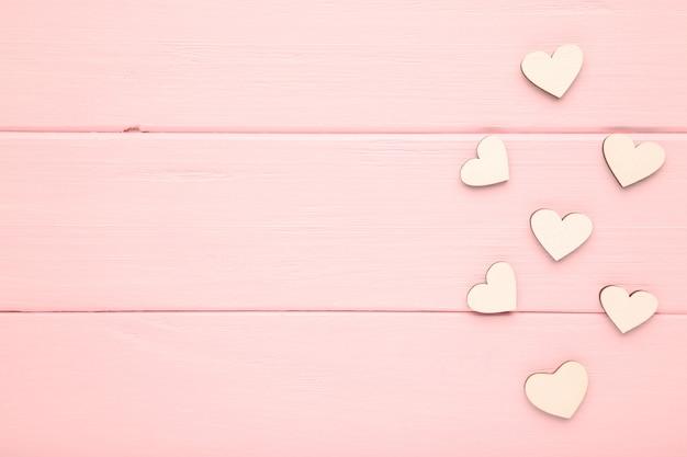 Corazones blancos sobre un fondo rosa. corazones de madera