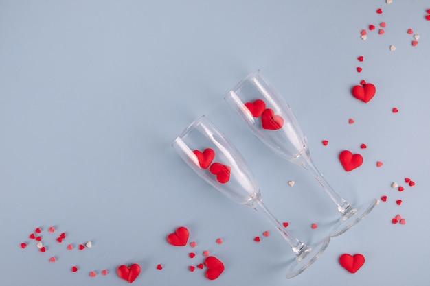 Corazones de caramelo rojo y dos copas de champán en mesa azul pastel