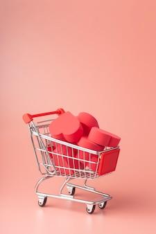 Corazones en carro de compras y carro de supermercado sobre fondo de color. fondo para san valentín (14 de febrero) y amor.