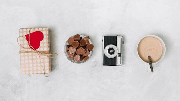 Corazones de chocolate, caja de regalo, cámara y taza de bebida.