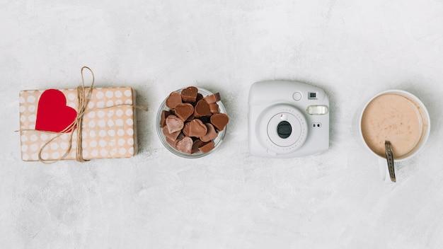 Corazones de chocolate, caja de regalo, camara y taza de bebida.