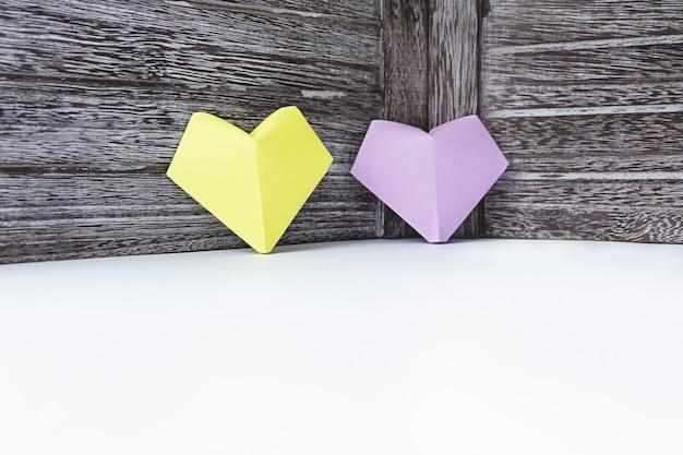 Los corazones de color lila y amarillo del papel están en el fondo de una tabla de madera oscura