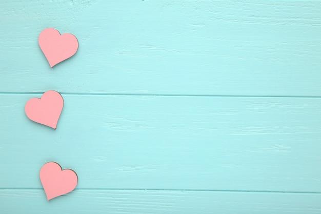 Corazones de color rosa sobre un fondo azul de madera.