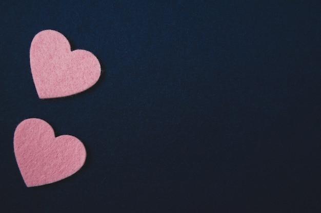 Corazones de color rosa sobre fondo azul oscuro de fieltro. día de san valentín
