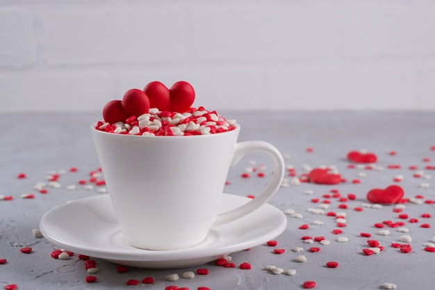 Corazones dulces rojos del caramelo de azúcar en una taza de café. decoración de concepto de amor y día de san valentín.