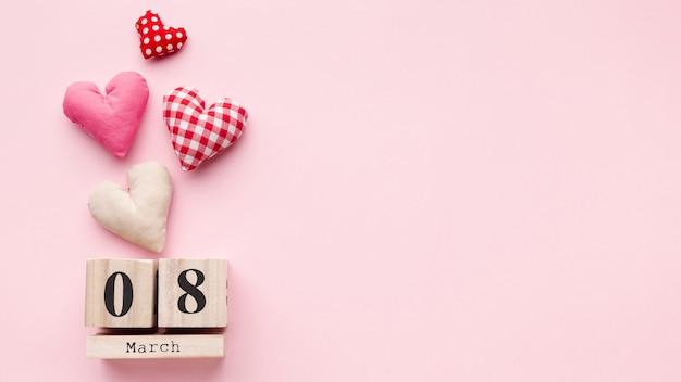 Corazones encantadores sobre fondo rosa con letras de 8 de marzo y espacio de copia