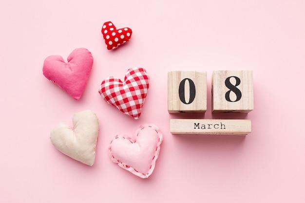 Corazones encantadores sobre fondo rosa con letras 8 de marzo