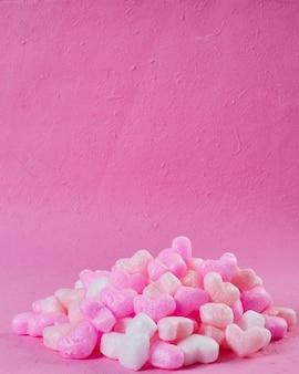 Corazones de espuma rosa fondo de papel rosa