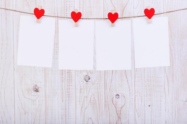 Corazones de fieltro rojo hecho a mano y papel blanco colgado de una cuerda con pinzas para la ropa