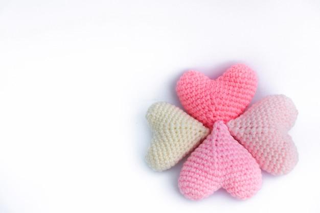 Los corazones de ganchillo de hilo de tejer forman coloridos patrones lindos hechos a mano sobre fondo aislado
