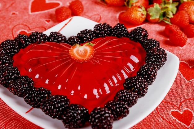 Corazones de gelatina de fresa con fresas y moras frescas.