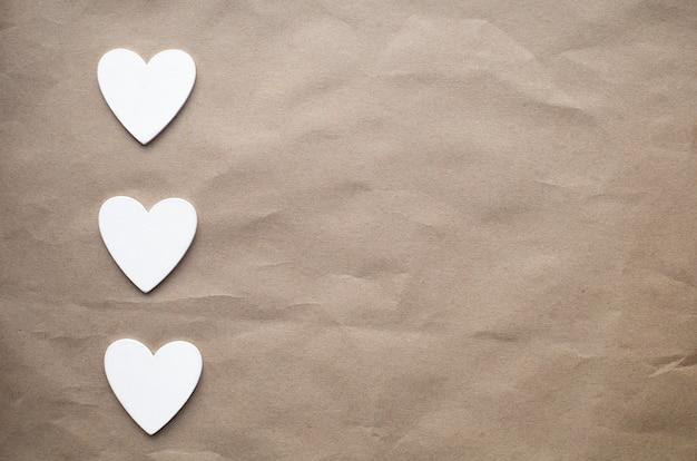 Corazones de madera blanca en fila vertical sobre fondo de papel kraft