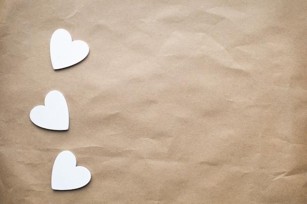 Corazones de madera blanca sobre fondo de papel kraft