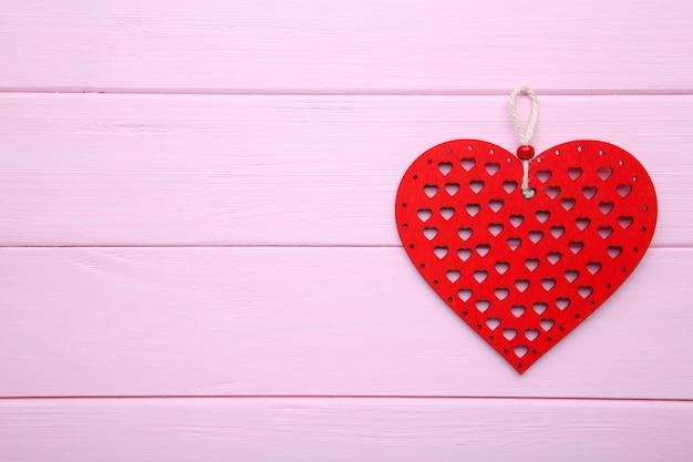 Corazones de madera roja sobre fondo de madera rosa