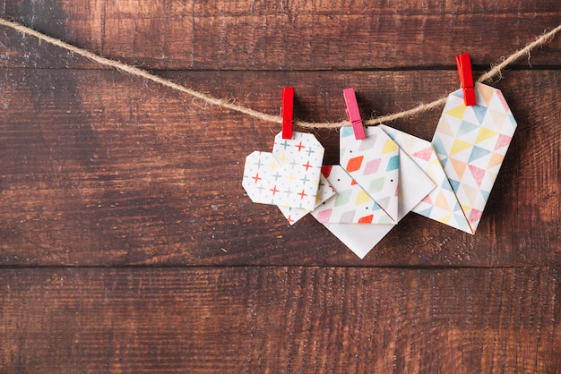 Corazones de papel con alfileres enganchados en hilo.