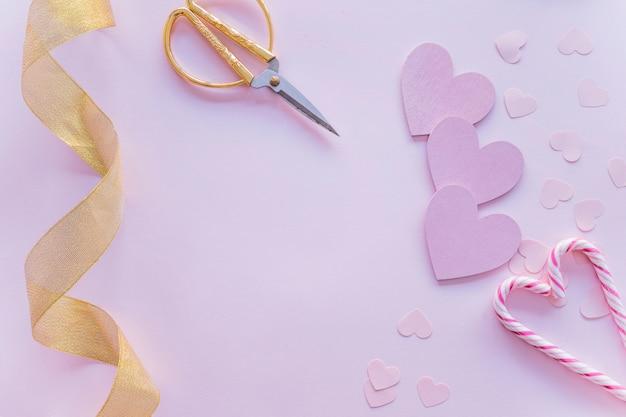 Corazones de papel con bastones de caramelo en la mesa